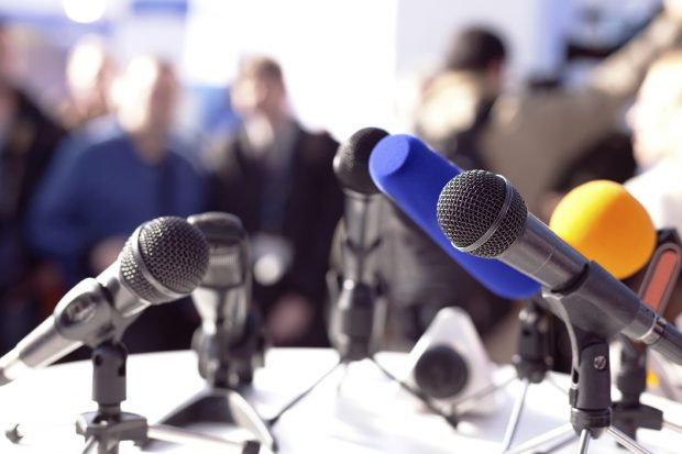 microphones and a blurred background of what looks like a press conference