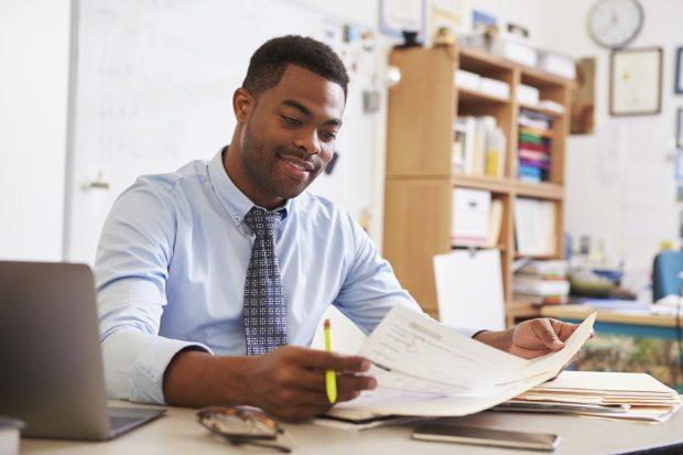a teacher holding a paper he is marking, and looking quite happy with himself about it