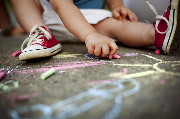 a child drawing on the floor with chalk