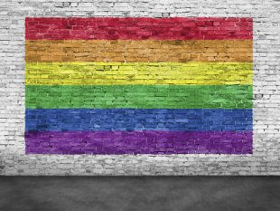 Rainbow flag painted over old white brick wall