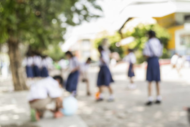 a blurred image of children playing in a playground wearing their school uniforms