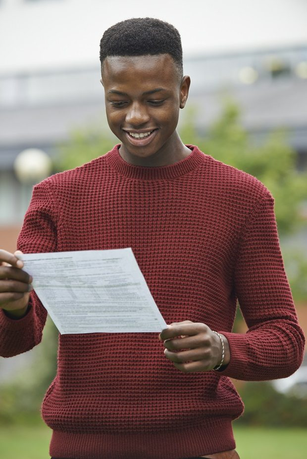 Student looking happy with a piece of paper showing his results