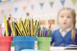A child looking at a bunch of pencils - bought with school funding
