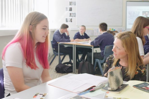 female pupil with pink hair sits next to teacher who appears to be explaining a piece of work