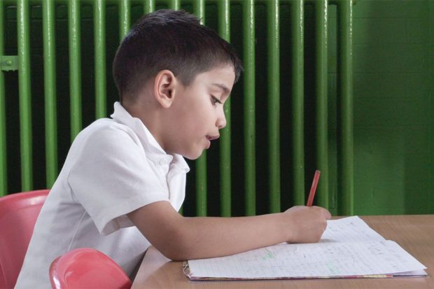 child filling in work pages with pen in a classroom