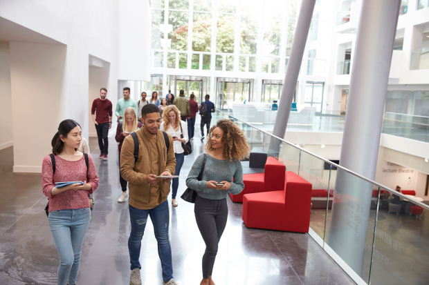 three university students walking in a lobby area