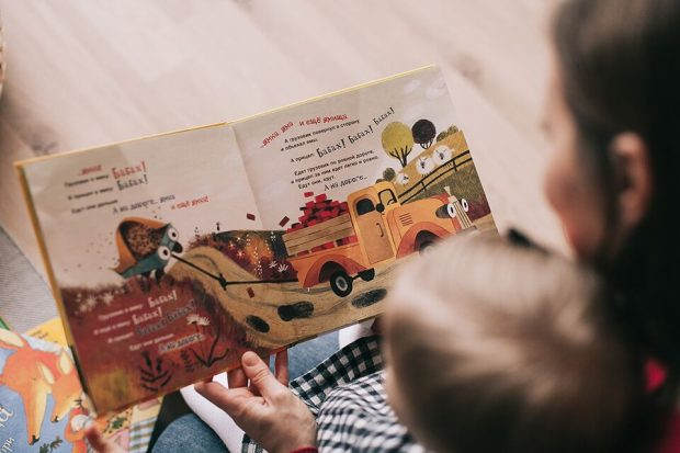 A child and parent reading a children's book with colourful pictures and text